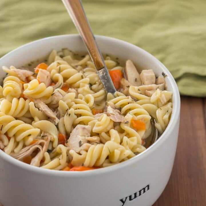 Instant Pot chicken noodle soup with gluten free pasta, sliced carrots, and herbes de Provence, in white bowl with wood handle spoon