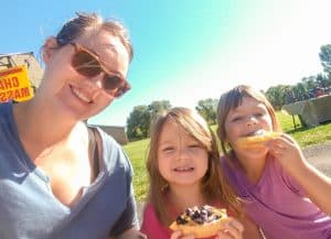 two girls and their mom eating gluten free waffle with blueberries and whipped cream from Sweet Nothings at Los Ranchos growers market in Albuquerque