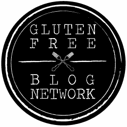 "Black circle with white border with two forks crossed in the center and text ""gluten free blog network"""