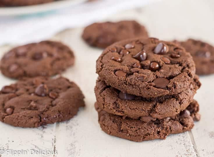 a stack with three gluten free dairy free double chocolate chip cookies on a white farm table with a few more cookies to the side