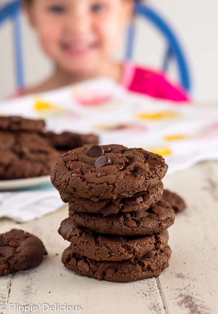 stack of gluten free double chocolate chip cookies with a girl in pink shirt in the background