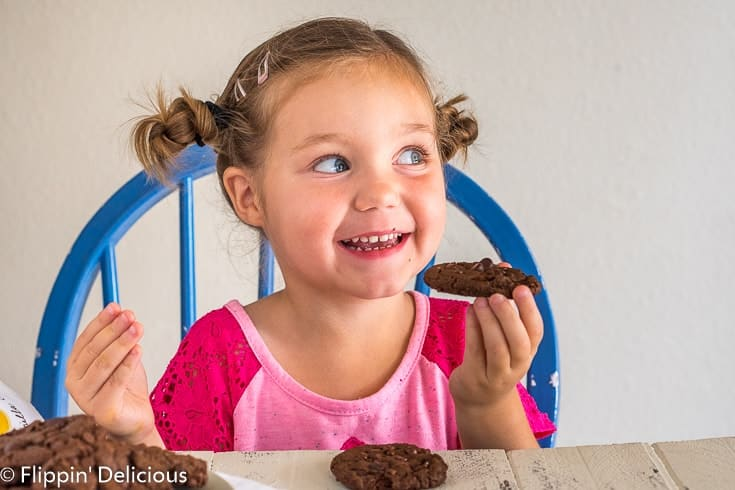 girl in pink shirt with two side buns excited to take a bite of a gluten free double chocolate chip cookie