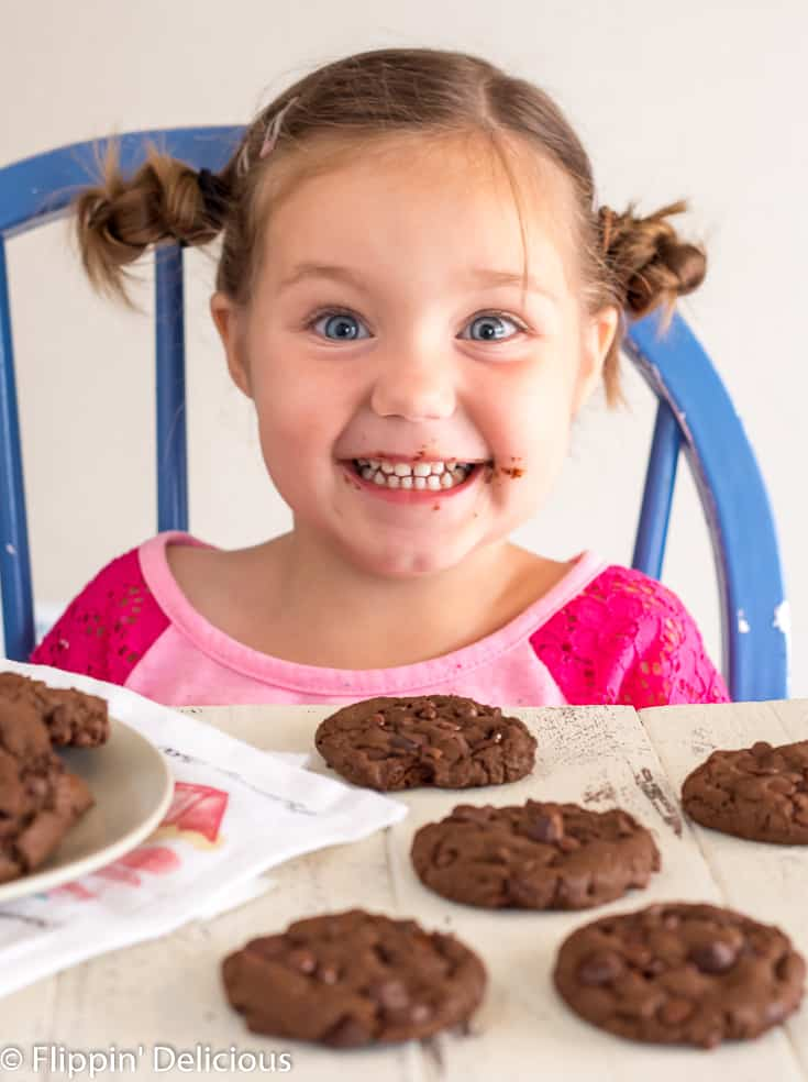 girl in pink shirt with two side buns smiling with chocolate on her cheek with gluten free double chocolate chip cookies in the foreground