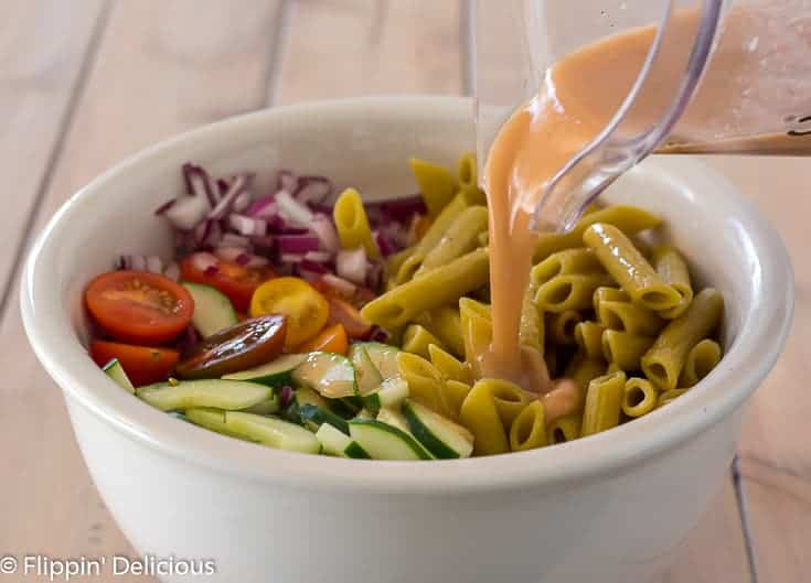 pouring homemade greek dressing from blender into large white bowl with gluten free green lentil penne, diced red onion, halved cherry tomatoes, and sliced cucumber