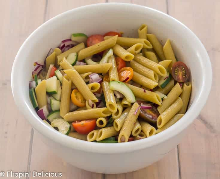 large white bowl with gluten free green lentil penne, diced red onion, halved cherry tomatoes, and sliced cucumber