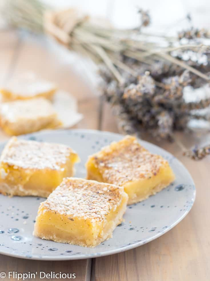 three gluten free lavender lemon bars on a blue plate with a bouquet of dried lavender in the background