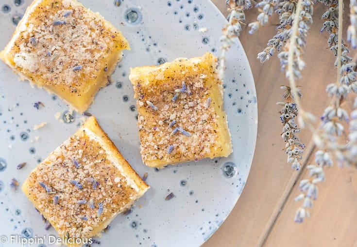 three gluten free lavender lemon bars on a blue plate beside a bouquet of dried lavender