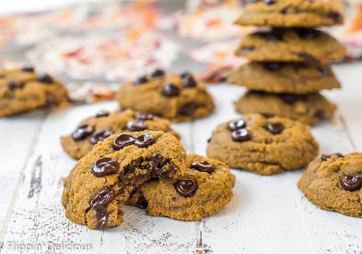 a gluten free vegan pumpkin chocolate chip cookie broken in half with melted chocolate on a white wood table, surrounded by more gluten free pumpkin chocolate chip cookies with a orange and brown patterned napkin in the background