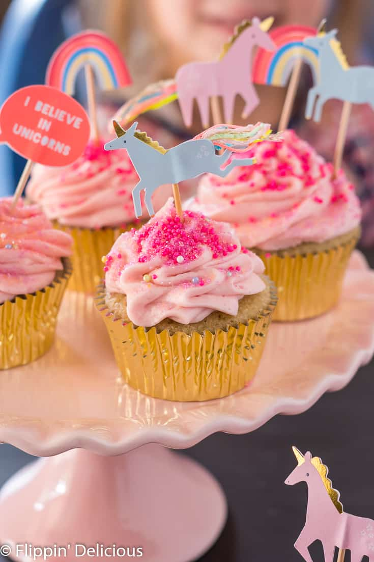 gluten free yellow cupcake in gold wrapper with pink strawberry buttercream and blue unicorn cupcake topper on a pink cake pedestal with more cupcakes in the background