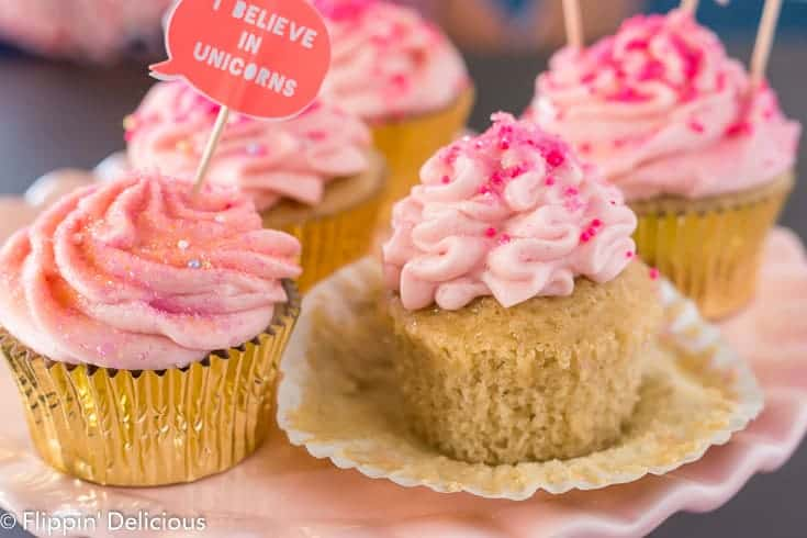 unwrapped gluten free yellow cupcake topped with pink strawberry frosting and pink sprinkles, on a pink cake pedestal with more pink frosted cupcakes in gold wrappers in the background