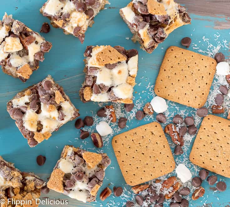 overhead view of vegan gluten free magic cookie bars with marshallows, pecans, coconut, graham crackers, and chocolate chips