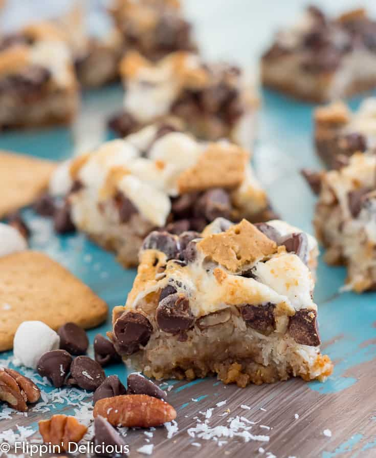 vegan gluten free magic cookie bars with marshmallows on a teal and gray table with schar honeygrams, pecans, chocolate chips, and marshallows