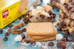 stack of schar honeygrams with marshmallows, chocolate chips, pecans, and shredded coconut with vegan gluten free magic cookie bar in the background