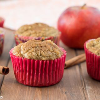 gluten free apple cinnamon muffins on a wooden table with cinnamon sticks, an apple and a dish towel in the background