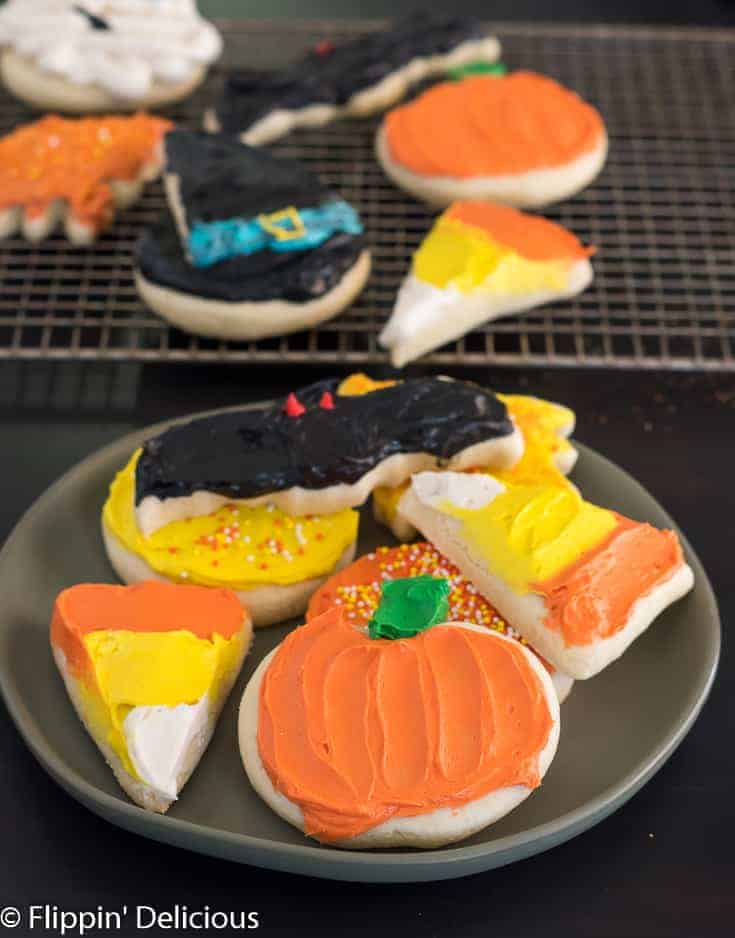 frosted gluten free Halloween sugar cookies including two candy corn sugar cookies, a pumpkin sugar cookie, a bat sugar cookie, fall leaf, and a witch hat sugar cookie, on a plate with more gluten free cut out cookies in the background