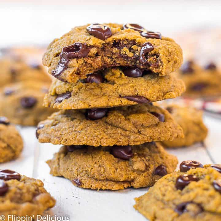 a stack of three gluten free vegan pumpkin chocolate chip cookies, with a bite taken out of the top pumpkin chocolate chip cookie on a white wood table, surrounded by more gluten free pumpkin chocolate chip cookies with a orange and brown patterned napkin in the background