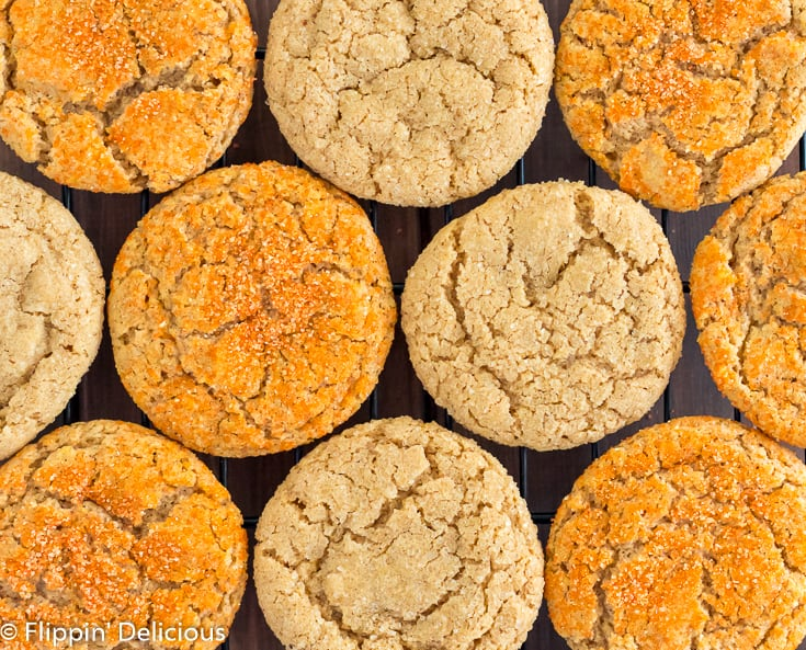 Overhead photo of vegan gluten free pumpkin sugar cookies on a black cooling rack, half sprinkled with orange sanding sugar and half with coarse raw sugar