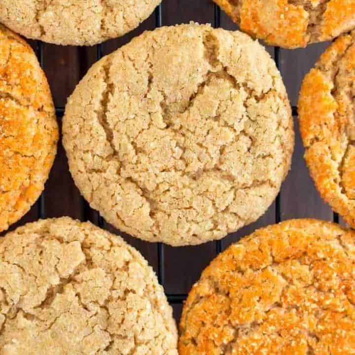Overhead photo of vegan gluten free pumpkin sugar cookies on a black cooling rack, half sprinkled with orange sanding sugar and half with coarse raw sugar