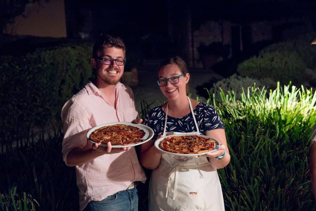 a man and woman holding gluten free pizzas at farewell night at jovial gluten free getaway in lucca italy