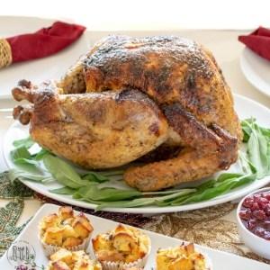 gluten free brined turkey on a platter with green herbs underneath