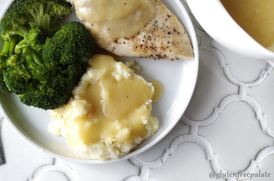 gluten free gravy over mashed potatoes and chicken breast beside broccoli on white plate