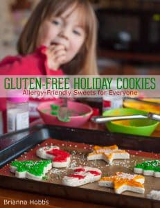 """girl eating gluten free sugar cookies with text overlay """"Gluten Free Holiday Cookies"""""""