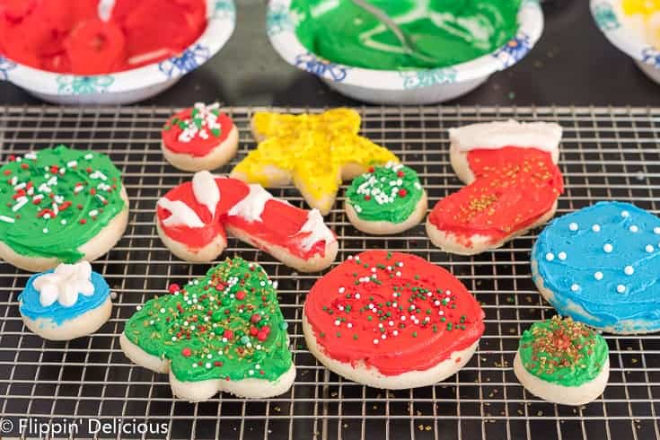 gluten free sugar cookie cutouts shaped like holiday tree, cane, stocking, and star on a cooling rack, topped with green, red, yellow, and white frosting and holiday sprinkles