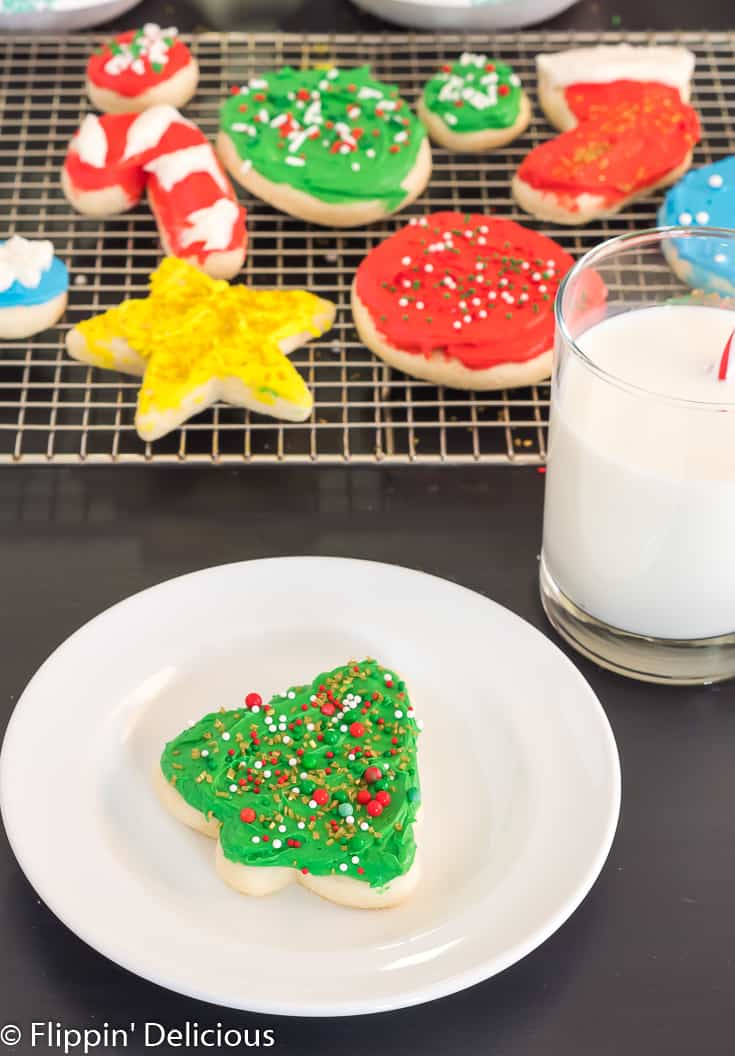 gluten free sugar cookie cutout shaped like a holiday tree with green frosting and sprinkles, on a white plate beside a glass of milk with a red and white striped straw with a cooling rack full of gluten free sugar cookie cutouts in the background
