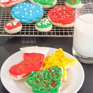 gluten free sugar cookie cutout shaped like a holiday tree, christmas stocking, and star, each topped with frosting and sprinkles, on a white plate beside a glass of milk with a red and white striped straw with a cooling rack full of gluten free sugar cookie cutouts in the background