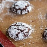 gluten free chocolate crinkle cookies covered in powdered sugar on a silicone baking mat