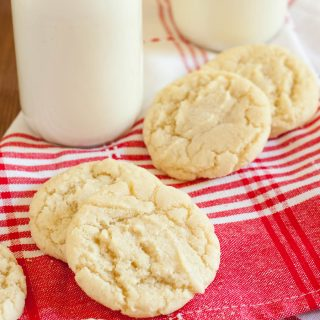 gluten free sugar cookies on a red plaid napkin next to glass of milk