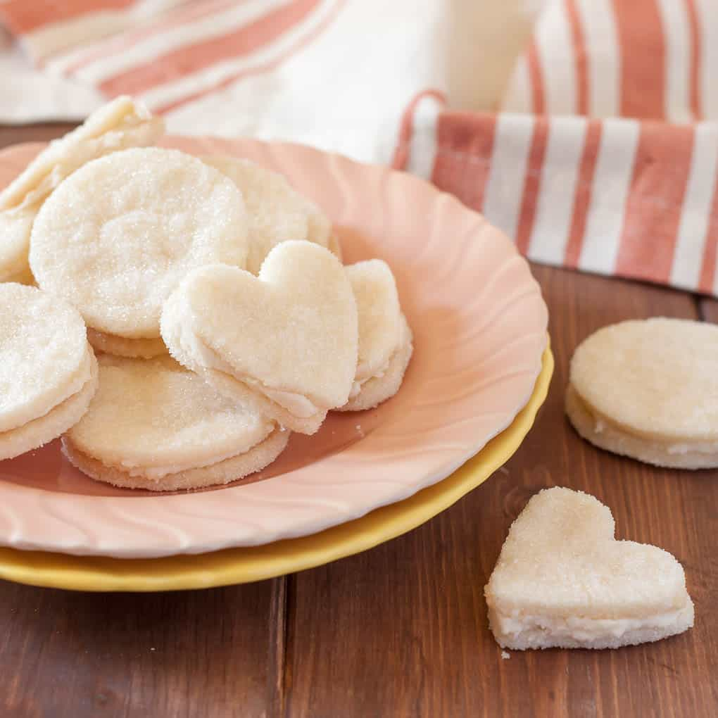 gluten free cream wafer sandwich cookies on a small peach plate with orange striped napkin in the background