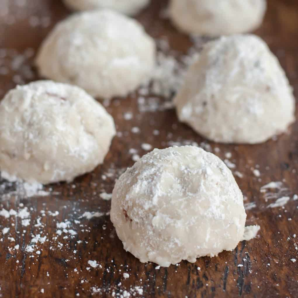 gluten free snowball cookies (also known as mexican wedding cookies or russian tea cakes) on a wooden table with powdered sugar