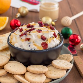 cranberry cream cheese dip drizzled with honey sprinkled with dried cranberries in black bowl on green plate filled with gluten free entertainment crackers on wooden table with sliced oranges, honey, and ornaments in the background