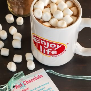 mug of vegan hot chocolate topped with marshmallows on brown table with jar of vegan hot chocolate mix and vegan hot chocolate mix label