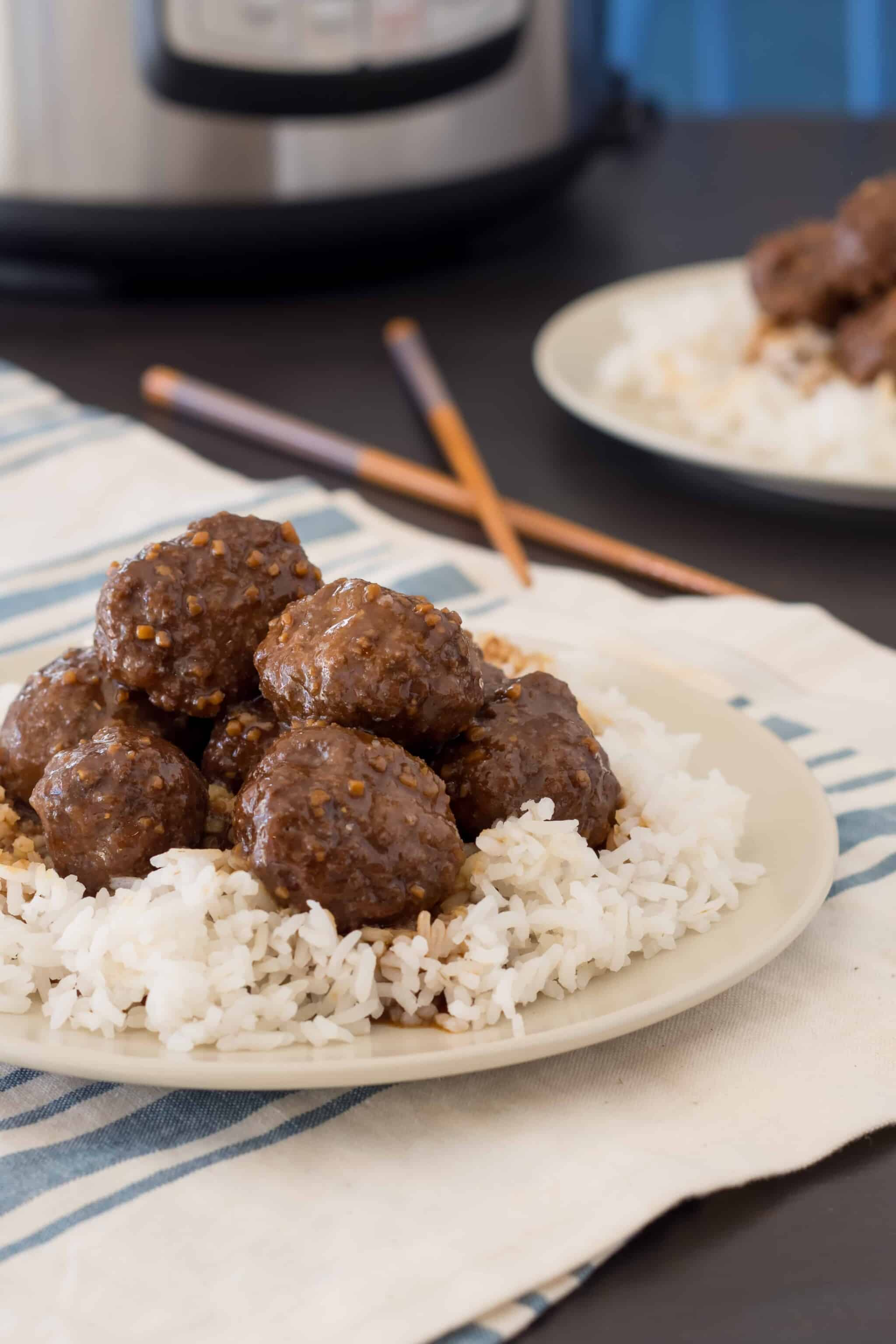 gluten free teriyaki meatballs on a bed of rice on a tan plate with an Instant pot and chopsticks in the background