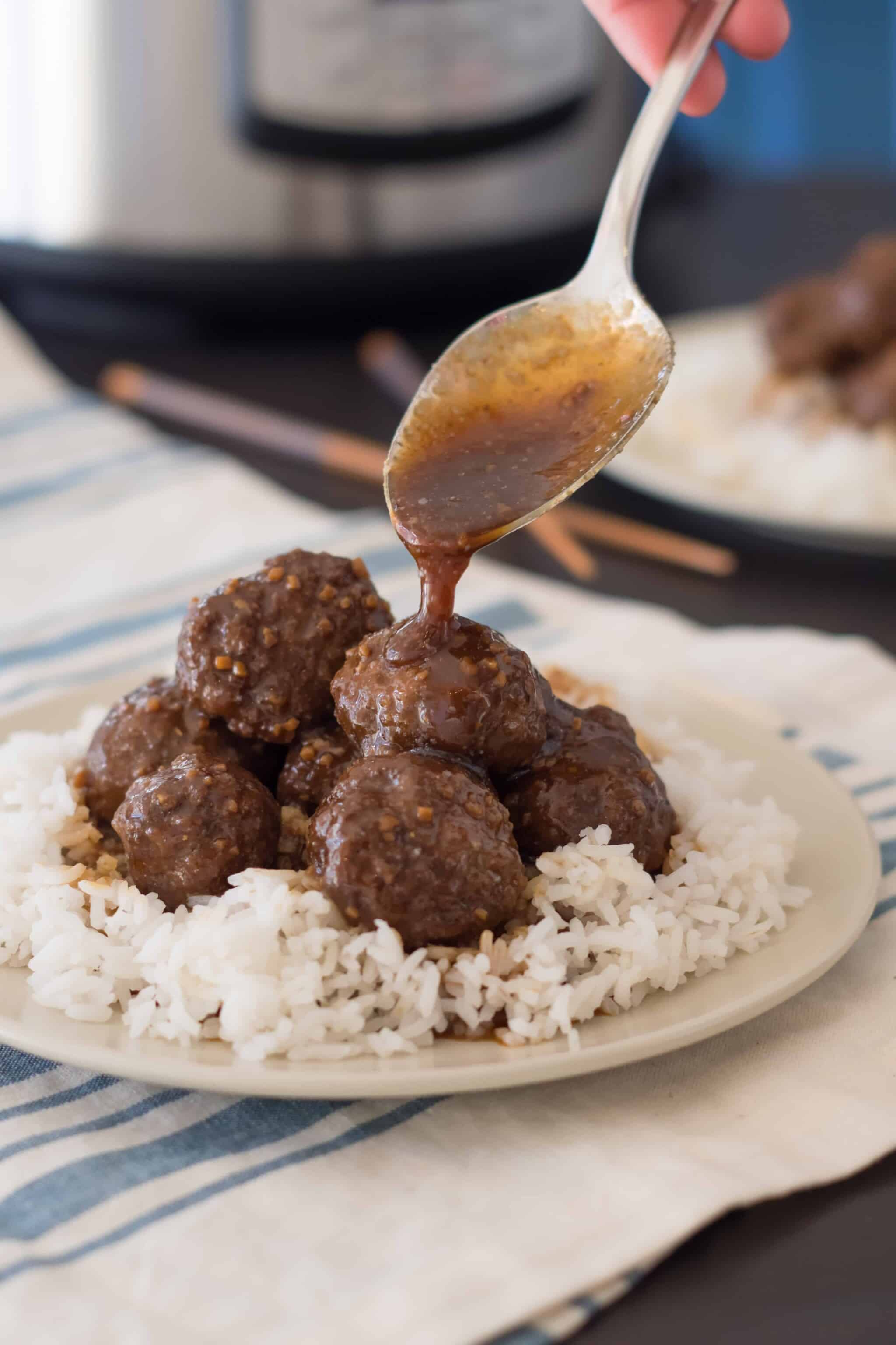 gluten free teriyaki meatballs on a bed of rice on a tan plate with a spoon pouring gluten free teriyaki sauce on top with an Instant pot and chopsticks in the background
