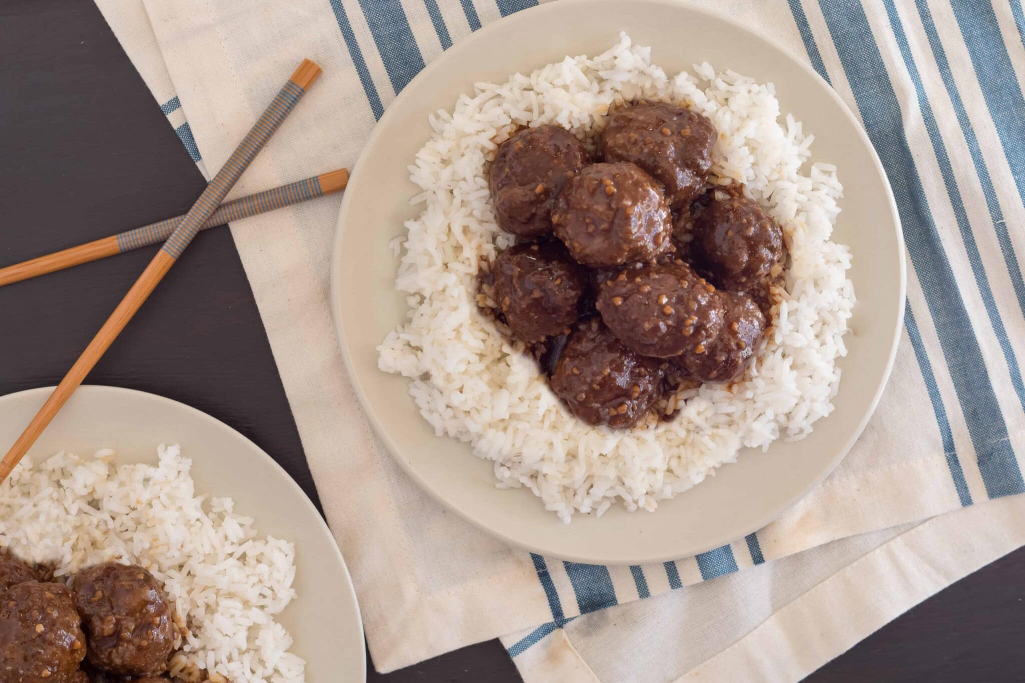 Overhead view of gluten free instant pot teriyaki meatballs on a bed of rice on top of a cream napkin with a blue stripe