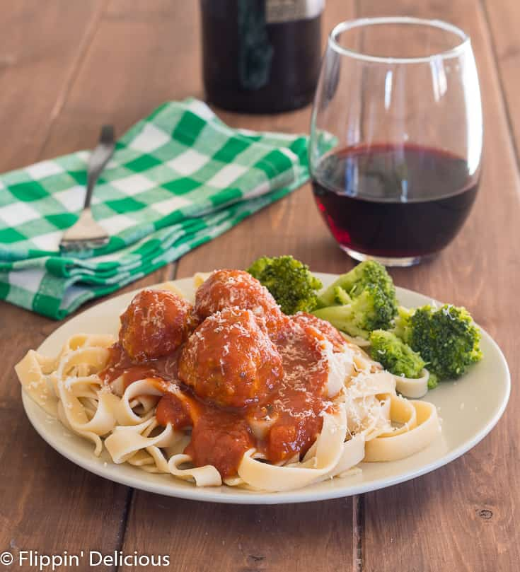 plate of gluten free instant pot meatballs with pasta and broccoli, with a glass of wine and green checked napkin in the background