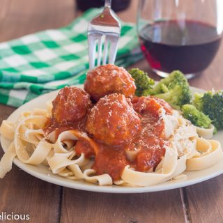 fork reaching for gluten free turkey meatball on a bed of gluten free fettucine with tomato sauce with a green and white checked napkin and glass of red wine in the background