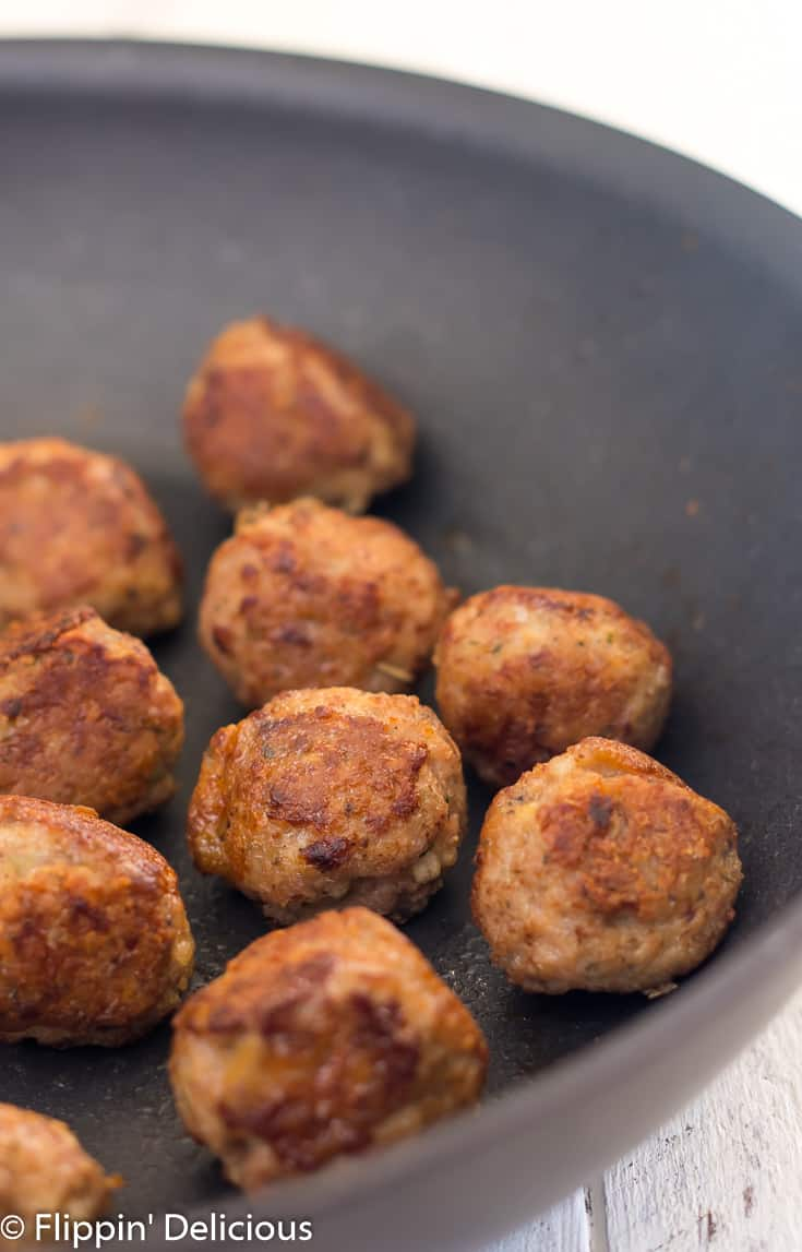 gluten free turkey meatballs browned and sitting in nonstick skillet