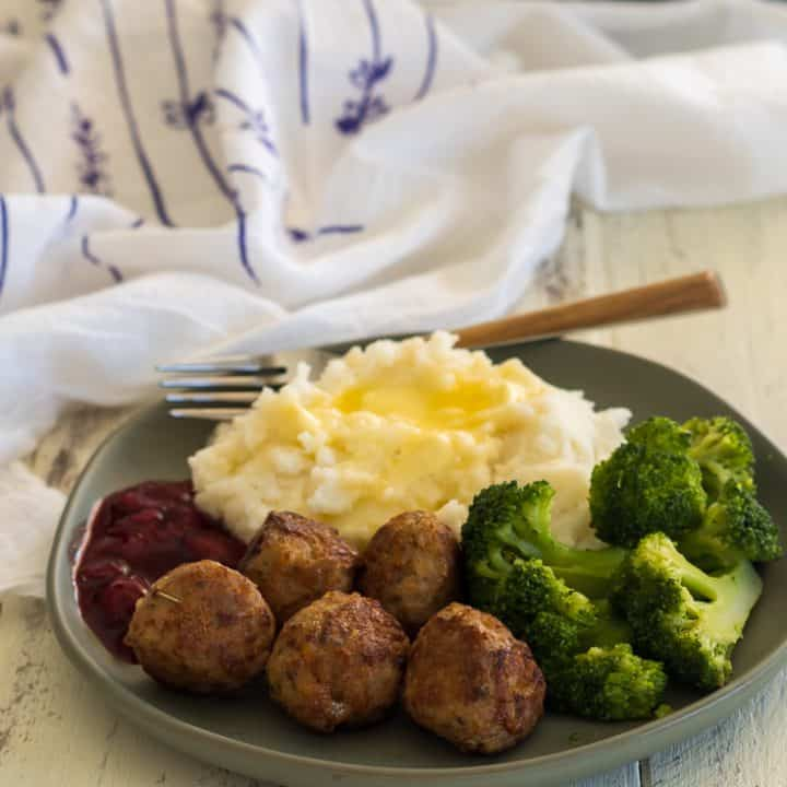green plate with five gluten free turkey meatballs, mashed potatoes, cherry sauce, and broccoli with a fork and white and purple dish towel in the background