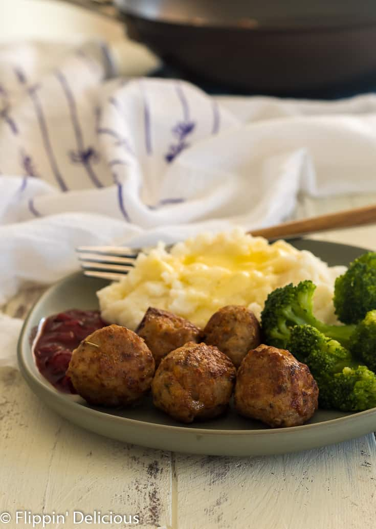 green plate with five sauteed turkey meatballs with a side of red berry sauce, steamed broccoli, and mashed potatoes with butter with a fork and white napkin with purple flowers