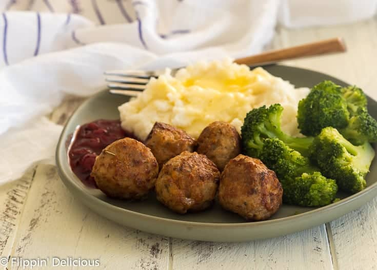 a green plate with five gluten free turkey meatballs, mashed potatoes, cherry sauce, and steamed broccoli on a white farmhouse table with a fork and a white dish towel with purple flower stems in the background