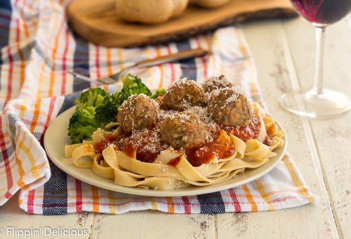 plate filled with gluten free pasta topped with marinara sauche and gluten free baked turkey meatballs, sprinkled with grated parmesan cheese.
