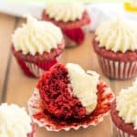 mini gluten free red velvet cupcakes, with one cupcake unwrapped and a bite taken on wood table