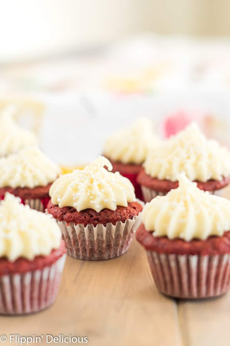 mini gluten free red velvet cupcakes in white cupcake wrappers frosted with cream cheese frosting with pearl sprinkles on a wood table
