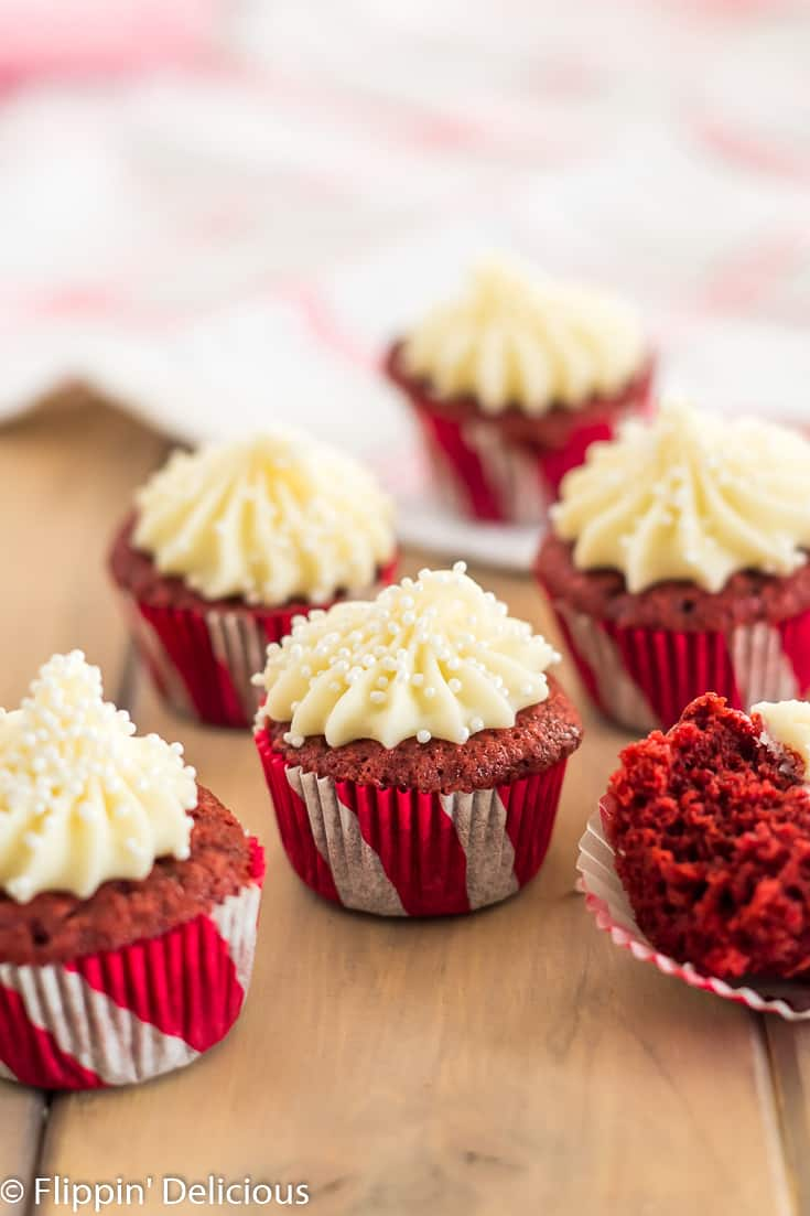 mini gluten free red velvet cupcakes in red and white candycane-striped cupcake wrappers frosted with cream cheese frosting with pearl sprinkles on a wood table