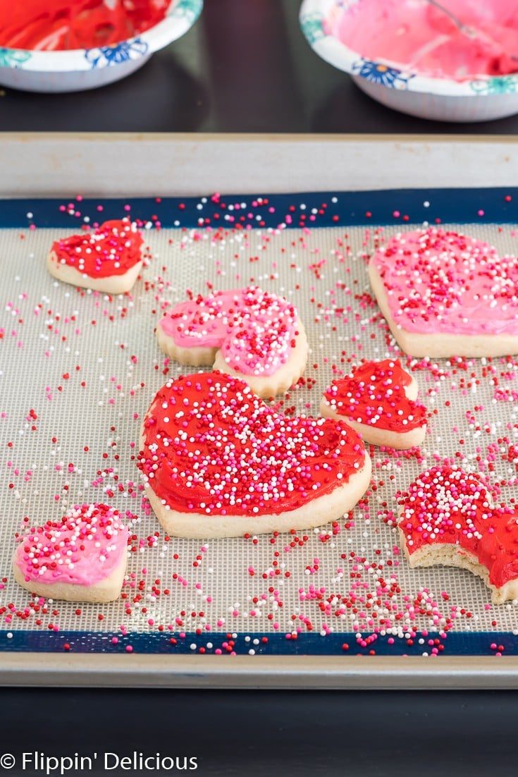 pink and red gluten free heart sugar cookies on a silicone baking sheet on a cookie sheet with pink, white, and red non pareil sprinkles