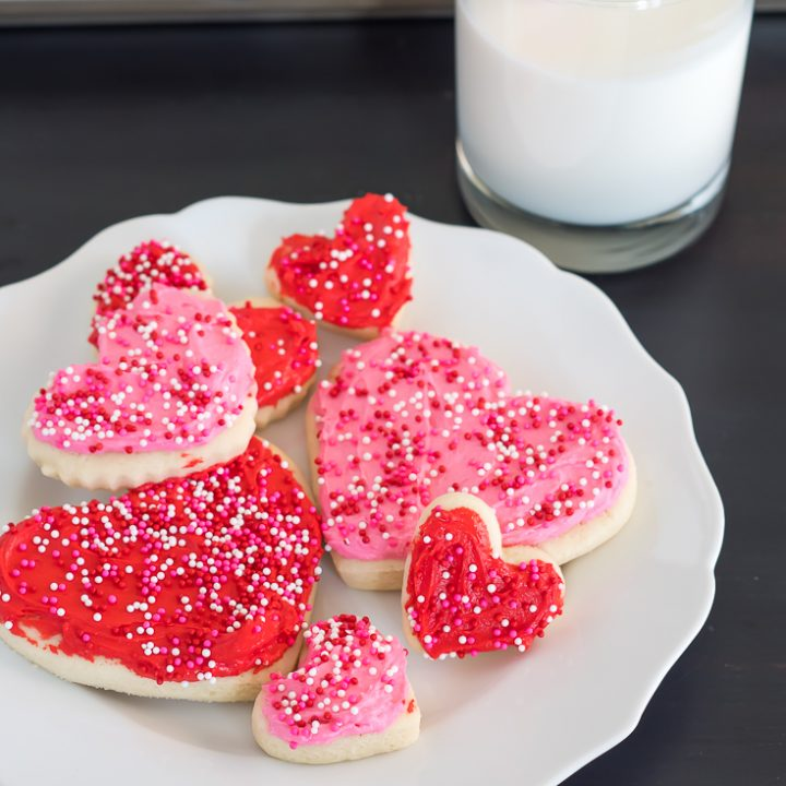 gluten free heart sugar cookies with pink and red frosting and pink, white, and red non pareil sprinkles on a white plate with a scalloped edge on a dark wooden table with a glass of milk with a white and red striped straw in the background